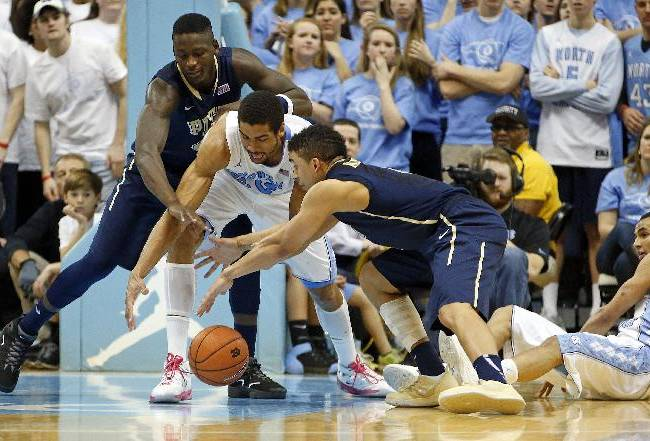 North Carolina's James Michael McAdoo, center, is sandwiched between Pittsburgh's Talib Zanna, left, and James Robinson, right, as the scramble for the ball during the second half of an NCAA college basketball game in Chapel Hill, N.C., Saturday, Feb. 15, 2014. North Carolina won 75-71