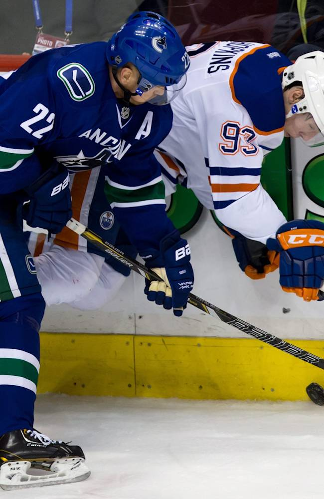 Vancouver Canucks' Daniel Sedin, left, of Sweden, checks Edmonton Oilers' Ryan Nugent-Hopkins during second period NHL hockey action in Vancouver, Canada, Sunday, Jan. 27, 2014
