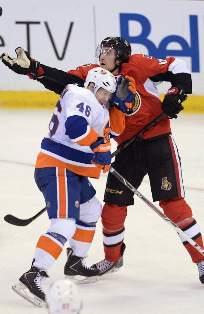 Ottawa Senators' Mark Stone reaches for an airborne puck as New York Islanders' Matt Donovan avoids a hit during the second period of an NHL hockey game in Ottawa, Ontario, on Wednesday, April 2, 2014