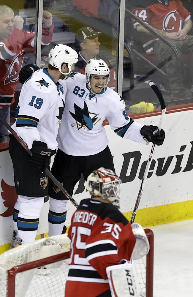 As New Jersey Devils goalie Cory Schneider (35) stands at the net, San Jose Sharks' Matt Nieto (83) celebrates his goal with teammate Joe Thornton (19) during the third period of an NHL hockey game Sunday, March. 2, 2014, in Newark, N.J. Sharks won 4-2