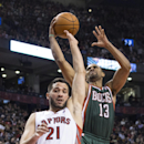 Milwaukee Bucks' Ramon Sessions, right, is fouled by Toronto Raptors' Greivis Vasquez during first half NBA basketball action in Toronto on Monday, April 14, 2014 The Associated Press