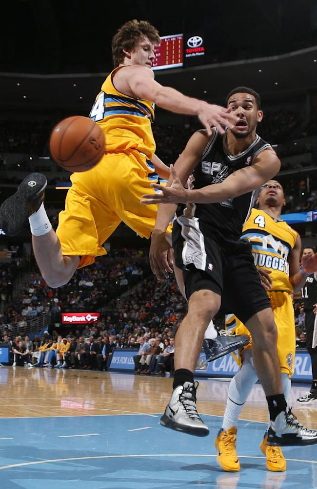 San Antonio Spurs guard Cory Joseph, right, passes ball as he drives the lane past Denver Nuggets forward Jan Vesely, of the Czech Republic, in the fourth quarter of the Spurs' 133-102 victory in an NBA basketball game in Denver, Friday, March 28, 2014