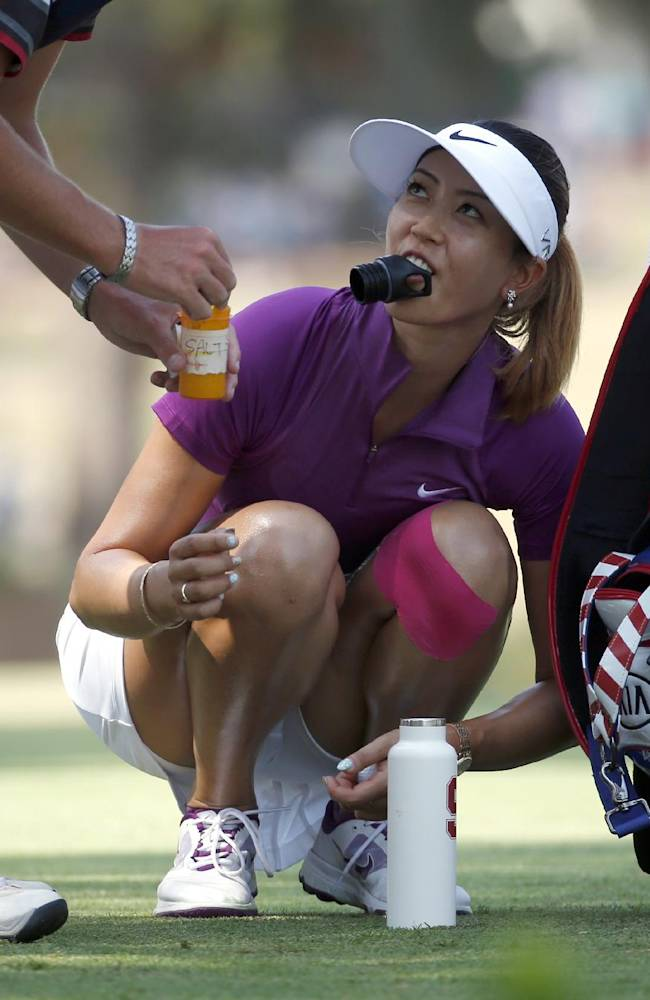 Michelle Wie gets some water as she waits to hit on the second hole during the second round of the U.S. Women's Open golf tournament in Pinehurst, N.C., Friday, June 20, 2014