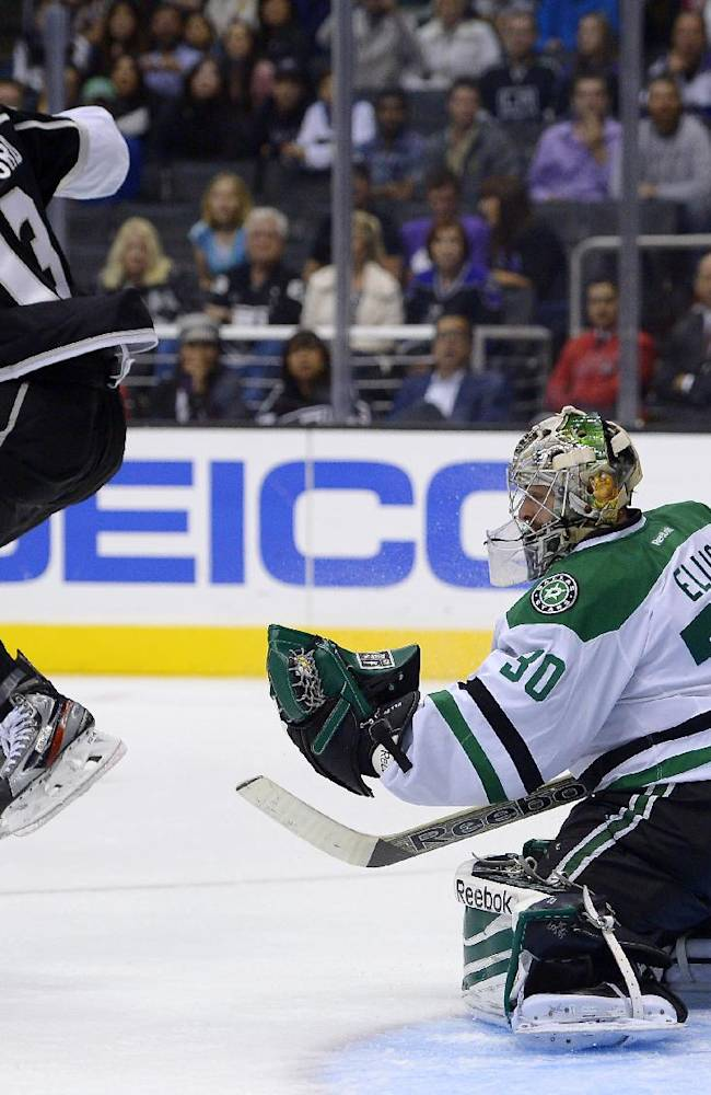 Los Angeles Kings left wing Kyle Clifford, left, jumps out of the way of a shot as Dallas Stars goalie Dan Ellis makes a glove save during the second period of their NHL hockey game, Saturday, Oct. 19, 2013, in Los Angeles, Calif