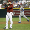 Arizona Diamondbacks' Trevor Cahill, left, waits for a new baseball as Los Angeles Dodgers' Adrian Gonzalez rounds the bases after hitting a three-run home run during the third inning of a baseball game on Sunday, April 13, 2014, in Phoenix The Associated