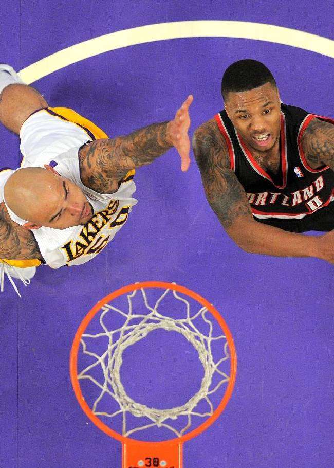 Portland Trail Blazers guard Damian Lillard, right, puts up a shot as Los Angeles Lakers center Robert Sacre defends during the second half of an NBA basketball game, Sunday, Dec. 1, 2013, in Los Angeles