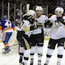 Pittsburgh Penguins' Sidney Crosby (87) celebrates his overtime goal with Kris Letang (58) and James Neal (18) as Islanders' Calvin de Haan (44) skates away during an NHL hockey game on Tuesday, Dec. 3, 2013, in Uniondale, N.Y. The Penguins won 3-2 The As