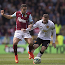 Burnley's Danny Ings, left, fights for the ball against Manchester United's Wayne Rooney during their English Premier League soccer match at Turf Moor Stadium, Burnley, England, Saturday Aug. 30, 2014
