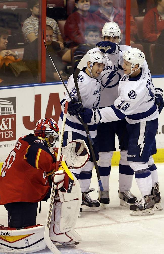 Tampa Bay Lightning center Tyler Johnson (9) is congratulated by teammates after scoring against Florida Panthers goalie Scott Clemmensen (30) during the second period of an NHL hockey game in Sunrise, Fla., Monday, Dec. 23, 2013