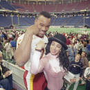 """FILE- In this Jan. 22, 1992, file photo, Washington Redskins defensive end Charles Mann compares muscles with television personality Julie Brown during Super Bowl XXVI Media Day at the Metrodome in Minneapolis. More than 5,500 journalists, psuedo-journalists and other credentialed """"media"""" are expected to gather for Tuesday, Jan. 27, 2015, Media Day at the US Airways Center. (AP Photo/David Longstreath, File)"""