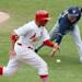 Milwaukee starting pitcher Kyle Lohse is unable to barehand a bunt by Cardinals' Pete Kozma that scored Jon Jay, left, in the fourth inning during the MLB National League baseball game between the St. Louis Cardinals and the Milwaukee Brewers on Sunday, May 19, 2013, at Busch Stadium in St. Louis