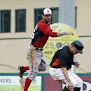 Washington Nationals' Jeff Kobernus, left, jumps over Miami Marlins' Jeff Baker after throwing to first base as Casey McGehee grounds into a double play in the fifth inning of an exhibition spring training baseball game, Monday, March 24, 2014, in Jupiter