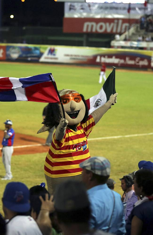 The Caribbean Series mascot waves the national flags representing the Dominican Republic and Mexico during the two countries Caribbean Series baseball semifinal game in Porlamar, Venezuela, Thursday, Feb. 6, 2014