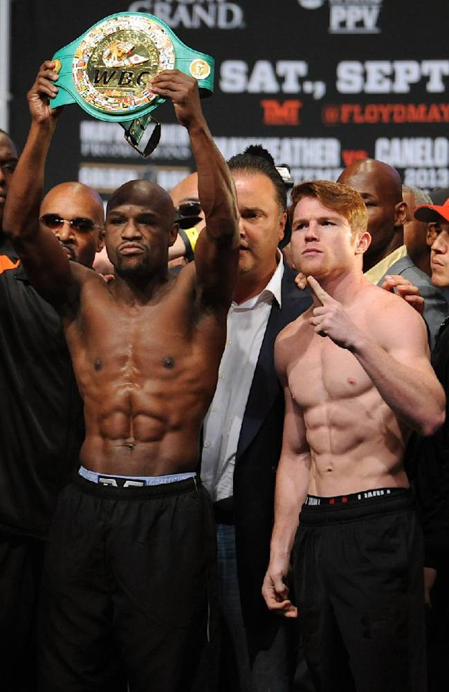 In this photo provided by the Las Vegas News Bureau, Floyd Mayweather Jr., left, and Canelo Alvarez pose the weigh-in for the Saturday boxing bout, Friday, Sept. 13, 2013, in Las Vegas. Mayweather's WBA super world and Alvarez's WBC junior middleweight titles are on the line