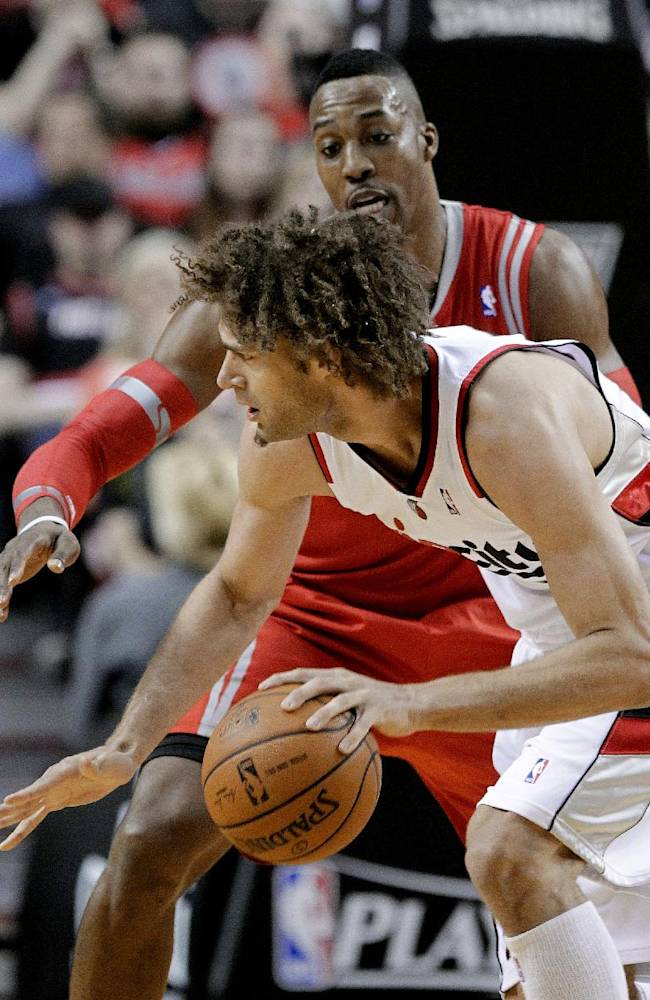 Portland Trail Blazers center Robin Lopez drives on Houston Rockets center Dwight Howard during the first half of Game 3 of an NBA basketball first-round playoff series in Portland, Ore., Friday, April 25, 2014
