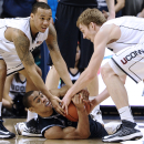 Connecticut's Shabazz Napier and Connecticut's Niels Giffey, right, reach for the ball from Georgetown's Markel Starks, center, during the first overtime of an NCAA college basketball game in Storrs, Conn., Wednesday, Feb. 27, 2013. Georgetown won 79-78. (AP Photo/Jessica Hill)
