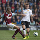 Burnley's Matthew Taylor, left, fights for the ball against Manchester United's Jonny Evans during their English Premier League soccer match at Turf Moor Stadium, Burnley, England, Saturday Aug. 30, 2014