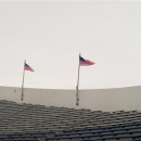 Michael Parker hangs one of dozens of American flags around the top of Liberty Bowl Memorial Stadium Friday, Dec. 28, 2012, in Memphis, Tenn., as crews prepare the stadium for the Liberty Bowl NCAA college football game between the Iowa State and Tulsa on New Year's Eve. (AP Photo/The Commercial Appeal, Brandon Dill)
