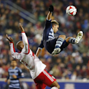 New York Red Bulls defender Jamison Olave (4) backs away from Sporting Kansas City forward Dom Dwyer (24) who attempts a header in the second half during an MLS playoff soccer match at Red Bull Arena in Harrison, N.J., Thursday, Oct. 30, 2014. The Red Bul