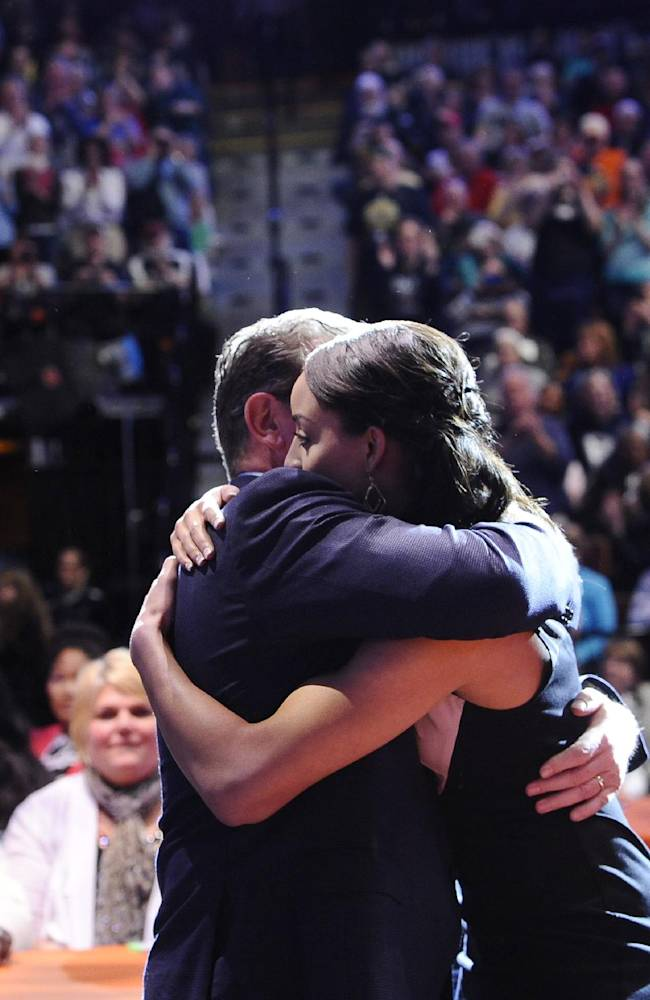 Connecticut head coach Geno Auriemma hugs player Bria Hartley after Hartley was chosen to go as the No. 7 pick to the Seattle Storm in the WNBA basketball draft in, Monday, April 14, 2014, in Uncasville, Conn