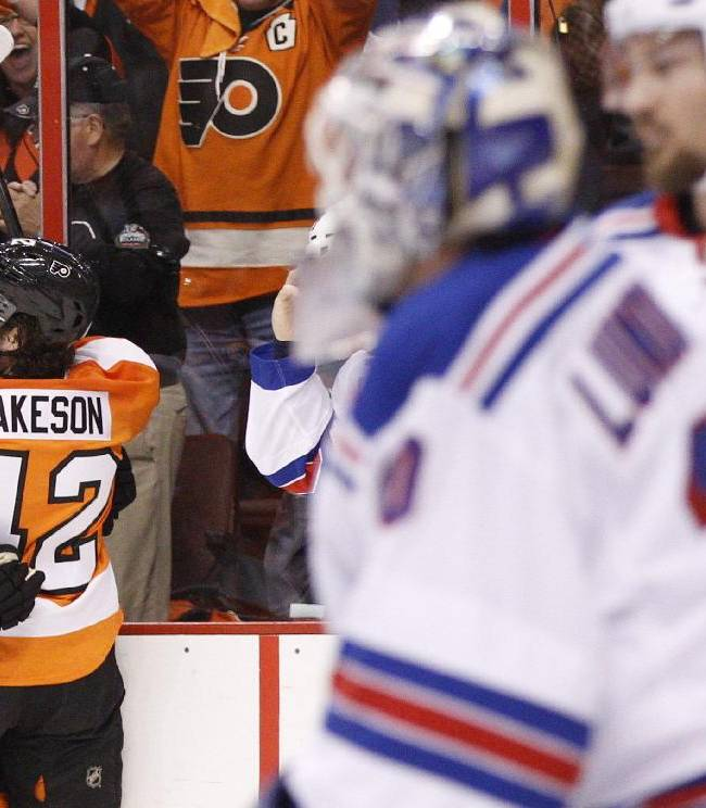 Philadelphia Flyers' Matt Read, left, celebrates his goal against New York Rangers' Henrik Lundqvist, front  right, of Sweden, with Jason Akeson (42) during the first period in Game 4 of an NHL hockey first-round playoff series on Friday, April 25, 2014, in Philadelphia
