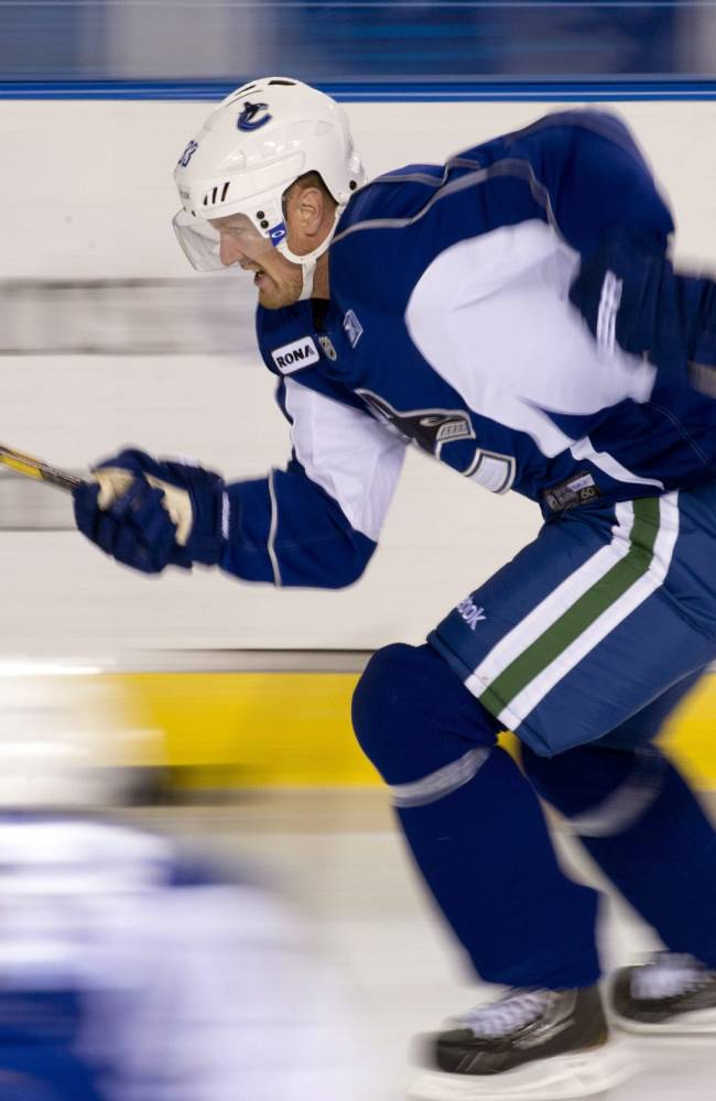 In this image taken with a slow shutter speed, Vancouver Canucks Henrik Sedin, of Sweden, skates during NHL hockey training camp at UBC Arena in Vancouver, British Columbia, Thursday, Sept. 12, 2013