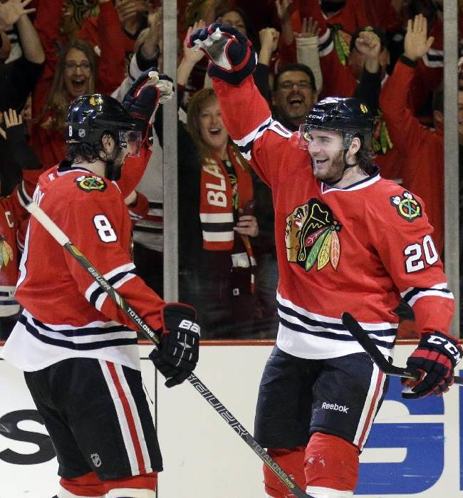 Chicago Blackhawks' Brandon Saad (20), right, celebrates with Nick Leddy (8) after scoring his goal during the second period in Game 2 of an NHL hockey second-round playoff series against the Minnesota Wild in Chicago, Sunday, May 4, 2014