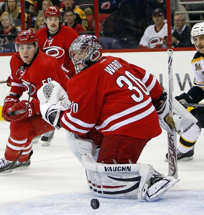 Carolina Hurricanes goalie Cam Ward (30) eyes the puck as teammate Chris Terry (58) and Boston Bruins' Patrice Bergeron (37) give chase during the first period of an NHL hockey game in Raleigh, N.C., Monday, Nov. 18, 2013