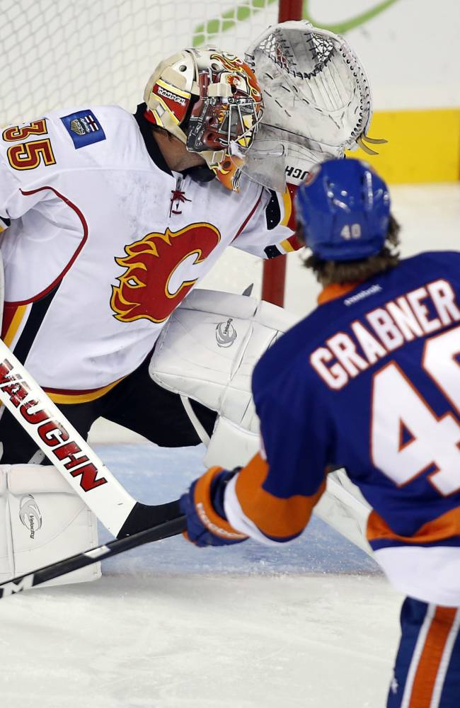 New York Islanders' Michael Grabner, right, from Austria, scores on Calgary Flames goalie Joey Macdonald during the first period of a preseason NHL hockey game Tuesday, Sept. 17, 2013, in Calgary, Alberta