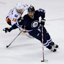 Calgary Flames' Brian McGrattan (16) and Winnipeg Jets' Dustin Byfuglien (33) fight for the puck during first period NHL hockey action in Winnipeg, Manitoba, Monday, Nov. 18, 2013 The Associated Press