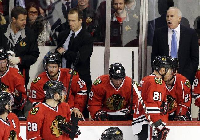 Chicago Blackhawks head coach Joel Quenneville, top right, talks to his team during the third period in Game 2 of an NHL hockey second-round playoff series against the Minnesota Wild in Chicago, Sunday, May 4, 2014. The Blackhawks won 4-1