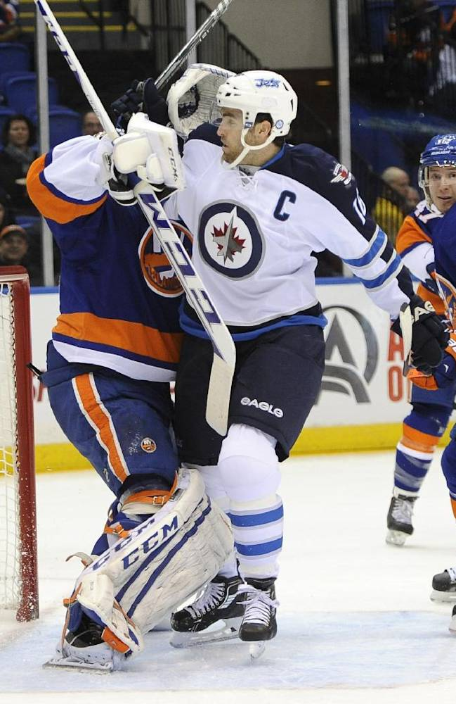 CORRECTS NAME AND NUMBER OF WINNIPEG JETS PLAYER - New York Islanders goalie Kevin Poulin, left,  battles with Winnipeg Jets' Andrew Ladd (16) in front of the net in the first period of an NHL hockey game on Wednesday, Nov. 27, 2013, in Uniondale, N.Y