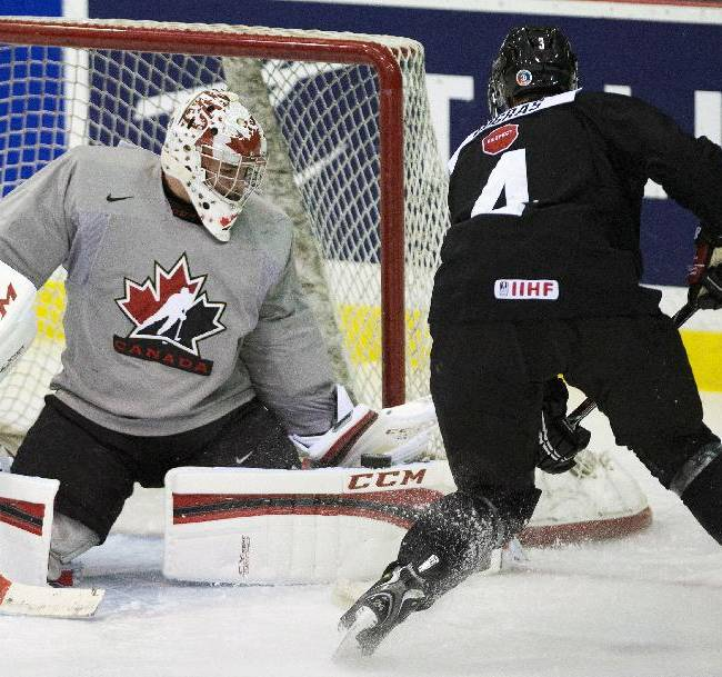 Team Canada goalie Jake Paterson, left, makes a save against Canada defenceman Chris Bigras (4) in practice during the juniors selection camp in Toronto on Friday, Dec. 13, 2013