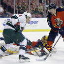 Minnesota Wild center Mikael Granlund, left, and Florida Panthers defenseman Aaron Ekblad (5) battle for the puck as goalie Roberto Luongo watches during the first period of an NHL hockey game, Monday, Nov. 24, 2014, in Sunrise, Fla The Associated Press