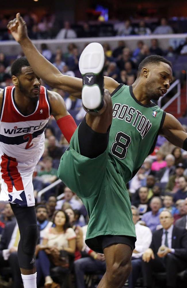 Washington Wizards guard John Wall (2) and Boston Celtics forward Jeff Green (8) land on the court after Wall's foul during Green's shot in the first half of an NBA basketball game Wednesday, April 2, 2014 in Washington. The Wizards won 118-92, and clinched a playoff berth