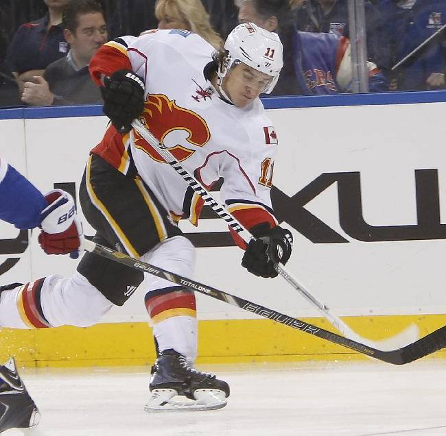 Calgary Flames' Mikael Backlund (11) shoots against New York Rangers' Ryan McDonagh, left, during the first period of an NHL hockey game Sunday, Dec. 15, 2013, in New York