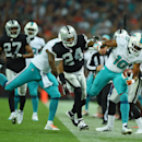Miami Dolphins' Brandon Gibson, right, is knocked out of play by Oakland Raiders' Charles Woodson during the NFL football game at Wembley Stadium in London, Sunday, Sept. 28, 2014. The Associated Press