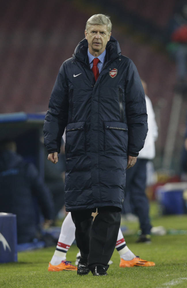 Arsenal's manager Arsene Wenger walks during a Champions League, group F soccer match, at the Naples San Paolo stadium, Italy, Wednesday, Dec. 11, 2013. Ten-man Arsenal advanced to the Champions League knockout phase for the 14th consecutive year despite a 2-0 loss Wednesday at Napoli, which was eliminated. Gonzalo Higuain scored in the 73rd minute but the San Paolo stadium was soon silenced when word arrived that Borussia Dortmund had scored a late goal in a 2-1 win at Marseille to win Group F