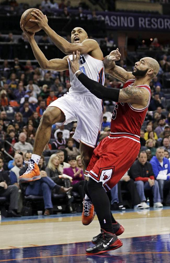 Charlotte Bobcats' Gerald Henderson, left, drives past Chicago Bulls' Carlos Boozer, right, during the first half of an NBA basketball game in Charlotte, N.C., Saturday, Jan. 25, 2014