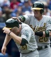Oakland Athletics teammates Josh Donaldson, right, celebrates with Brandon Moss, left, after scoring runs against the Toronto Blue Jays during ninth inning MLB American League baseball action in Toronto on Monday, August 12, 2013. (AP Photo/The Canadian Press, Nathan Denette)