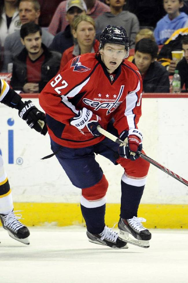Washington Capitals center Evgeny Kuznetsov (92), of Russia, works the puck up ice against Boston Bruins center Chris Kelly (23) during the first period of an NHL hockey game, Saturday, March 29, 2014, in Washington