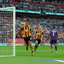 Hull City's Tom Huddlestone, left, celebrates after scoring against Sheffield United during their English FA Cup semifinal soccer match between Hull City and Sheffield United at Wembley Stadium, London, England, Sunday, April 13, 2014