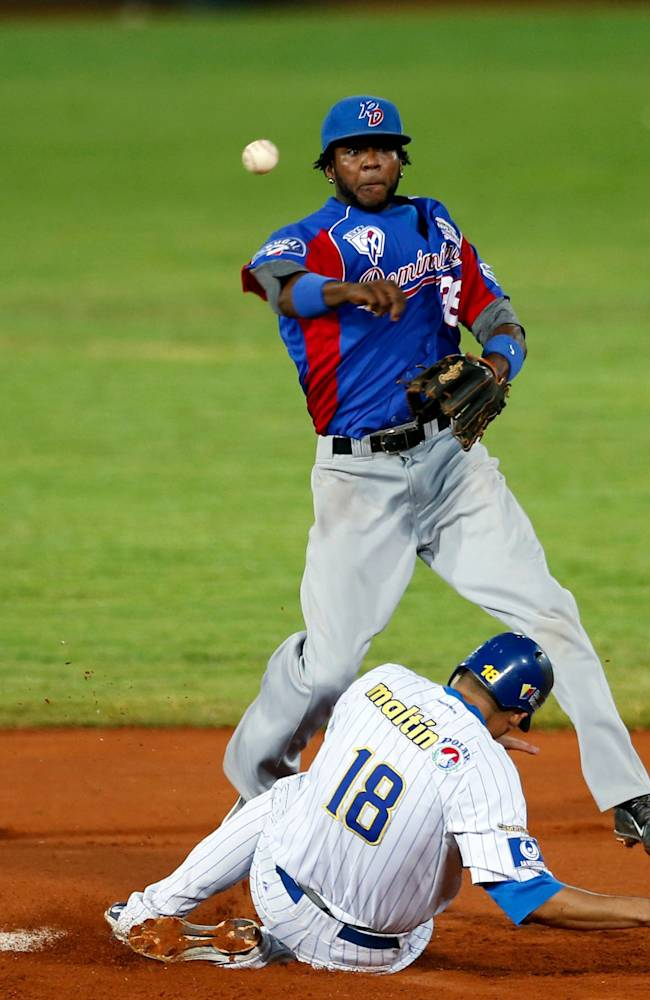 Dominican Republic shortstop Hector Gomez, top, releases the ball to first base after tagging out at second base Venezuela's infielder Mario Lisson, completing a double during a Caribbean Series baseball game in Porlamar, Venezuela, Tuesday, Feb. 4, 2014