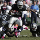 Oakland Raiders running back Darren McFadden (20) runs through a tackle-attempt by San Diego Chargers outside linebacker Jeremiah Attaochu (97) during the fourth quarter of an NFL football game in Oakland, Calif., Sunday, Oct. 12, 2014 The Associated Pres