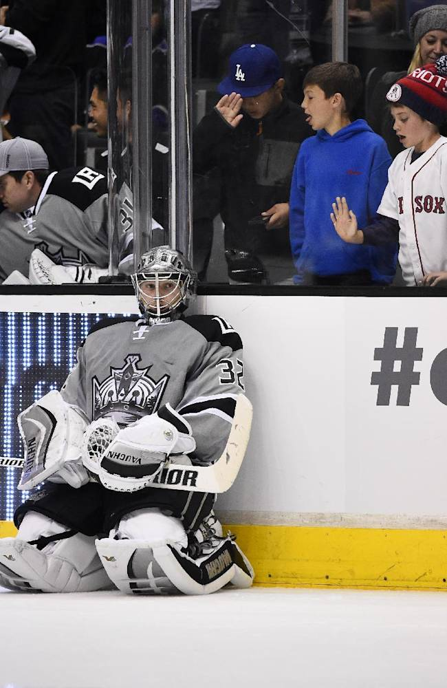 Los Angeles Kings goalie Jonathan Quick, left, waits for an overtime shootout to start as young fans look on during the third period of an NHL hockey game against the Anaheim Ducks, Saturday, April 12, 2014, in Los Angeles. The Ducks won 4-3