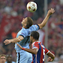 Manchester City's Edin Dzeko, left, and Bayern's Mehdi Benatia challenge for the ball during the Champions League group E soccer match between Bayern Munich and Manchester City in Munich, Germany, Wednesday Sept.17,2014