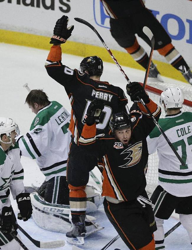 Anaheim Ducks' Matt Beleskey (39) and Corey Perry (10) celebrate a goal by Ryan Getzlaf in front of Dallas Stars goalie Kari Lehtonen (32), of Finland, during the first period in Game 1 of the first-round NHL hockey Stanley Cup playoff series on Wednesday, April 16, 2014, in Anaheim, Calif