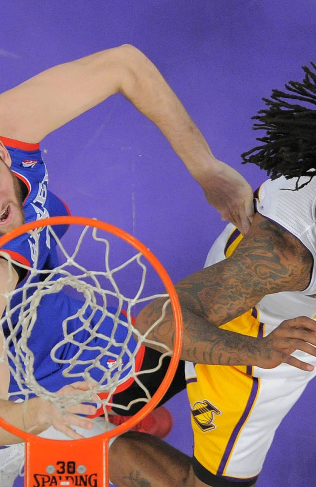 Philadelphia 76ers center Spencer Hawes, left, and Los Angeles Lakers center Jordan Hill battle for a rebound during the first half of an NBA basketball game, Sunday, Dec. 29, 2013, in Los Angeles