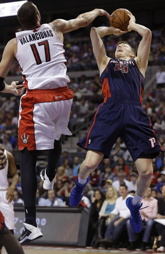 Detroit Pistons forward Kyle Singler (25) shoots over Toronto Raptors center Jonas Valanciunas (17) of Lithuania during the first half of an NBA basketball game in Auburn Hills, Mich., Sunday, April 13, 2014