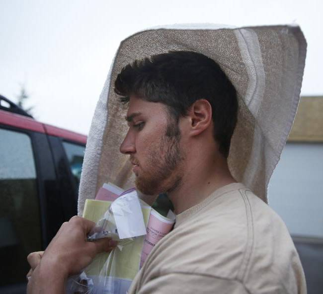 Former Minnesota quarterback Philip Nelson leaves the Blue Earth Co jail with a towel on his head after posting $20,000 bail in his assault case stemming from a fight outside a bar that left another former football player in critical condition with head injuries, in Mankato, Minn, Monday, May 12, 2014. Authorities say Nelson kicked Isaac Dallas Kolstad, 24, in the head after another man punched and knocked him to the ground early Sunday as bars were closing in Mankato